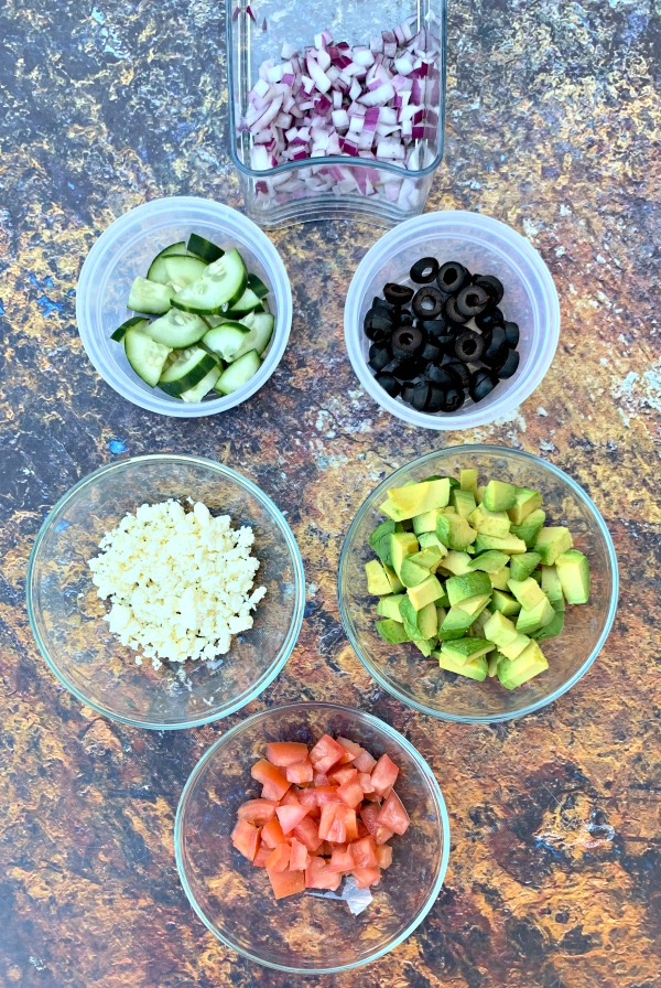 ingredients for keto zucchini noodle pasta salad in different bowls
