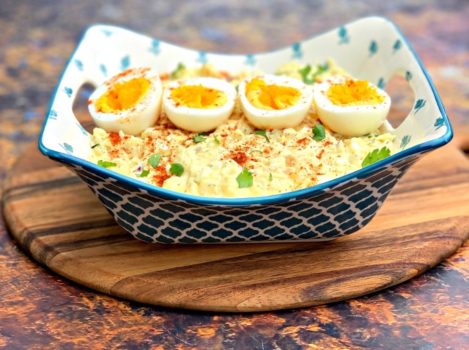 keto low carb potato salad with boiled eggs in a blue bowl on a wooden pizza paddle board