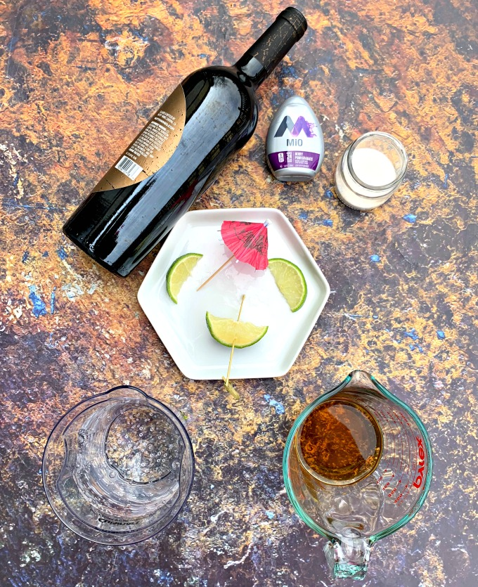 red wine, brandy, club soda, and limes on a flat surface