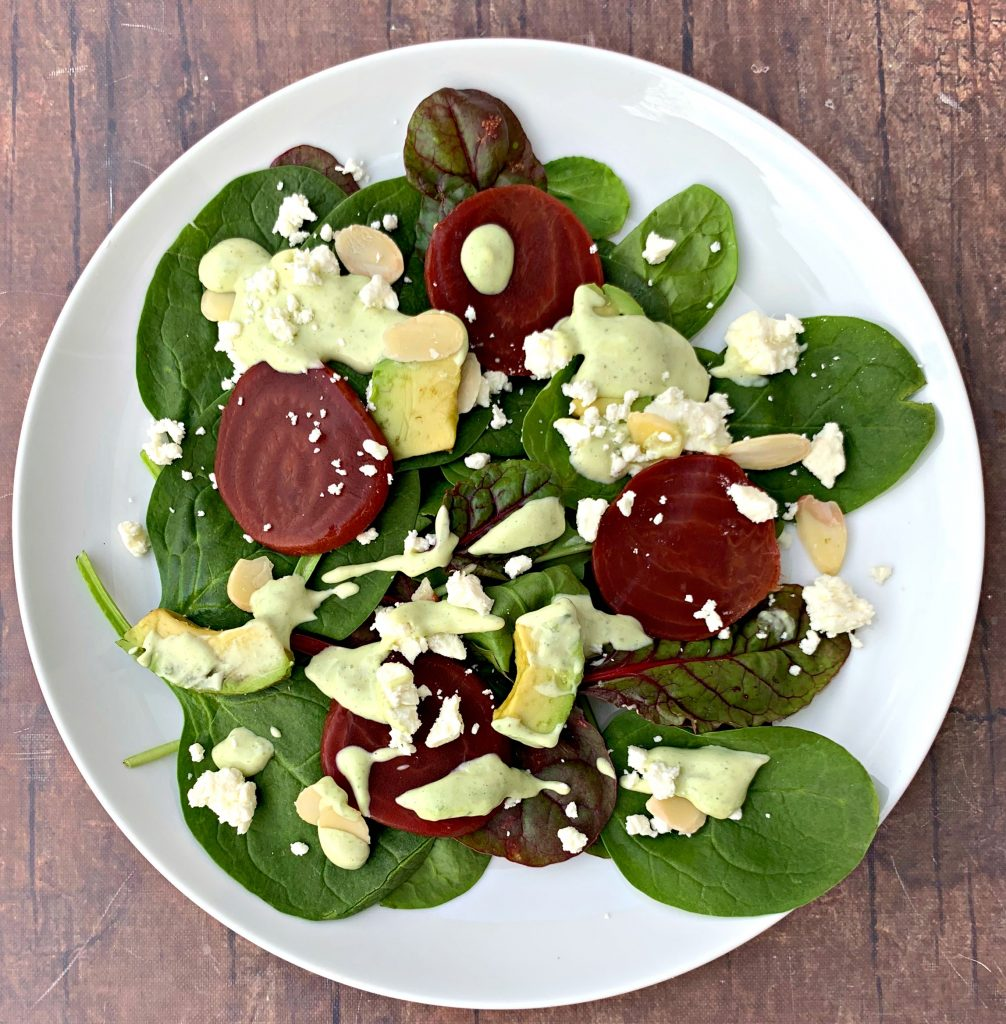 green goddess beet salad on a white plate with dressing