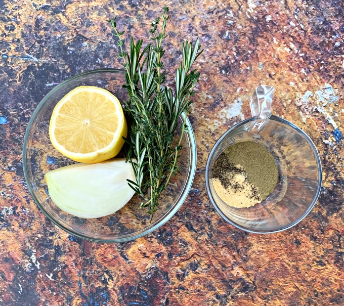 fresh lemon, onion, rosemary, and thyme in a glass bowl with seasonings for whole chicken
