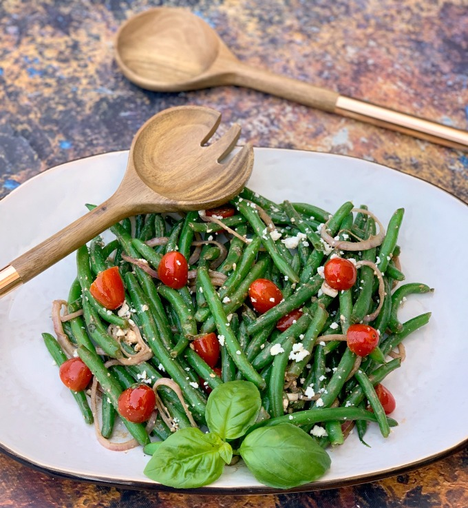 cold green bean salad with tomatoes and feta cheese on a white plate