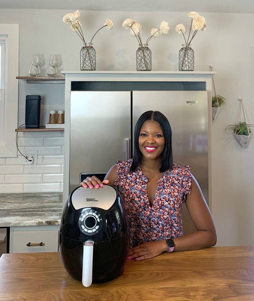 Brandi Crawford with an air fryer in a kitchen
