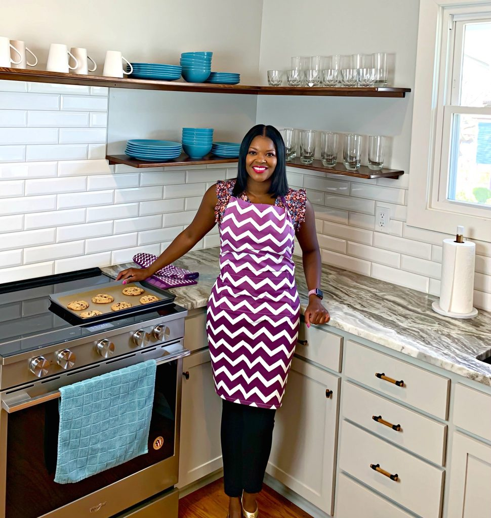Brandi Crawford standing in a kitchen at a stove with cookies