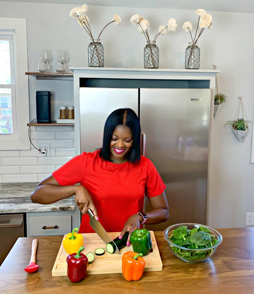Brandi Crawford slicing up vegetables in a kitchen