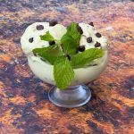 keto low carb mint chocolate ice cream in a glass bowl with chocolate chips