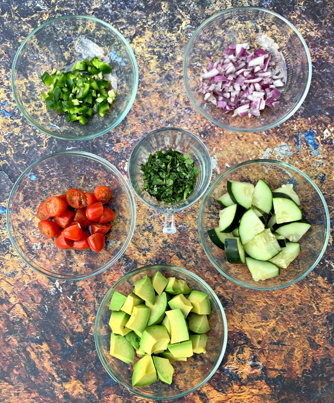 chopped jalapenos, onions, avocado, cucumbers, cilantro, and tomatoes in glass bowls on a flat surface