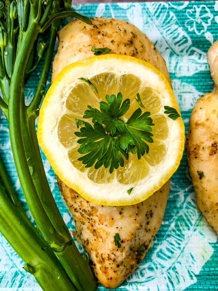air fryer chicken breast on a blue plate with broccoli and lemons