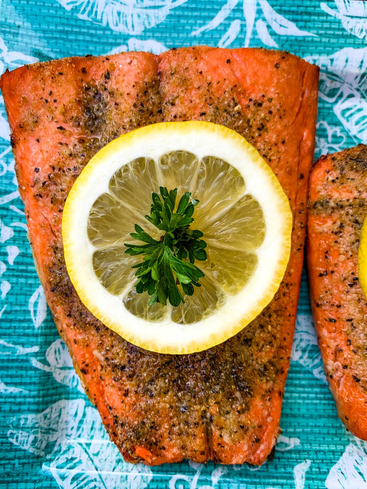 air fryer salmon on a blue plate with a fresh lemon size