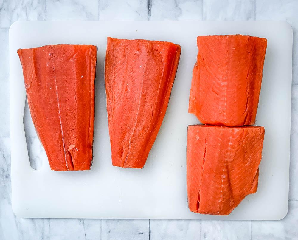 raw Alaskan salmon on a cutting board
