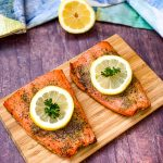 air fryer salmon on a wooden board with a fresh lemon size