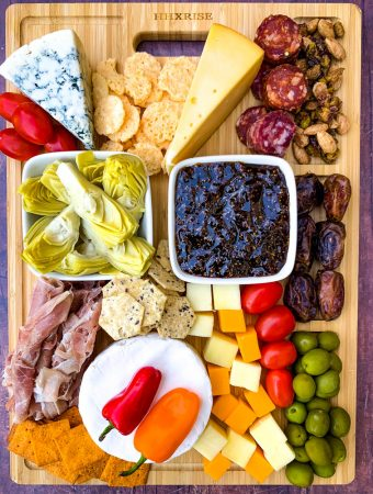 charcuterie board with artichokes, fig spread, cheese, and meat