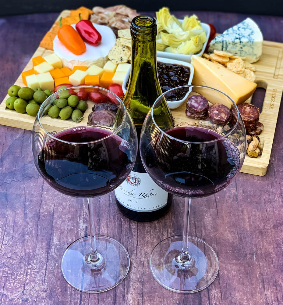 charcuterie board with artichokes, fig spread, cheese, and meat with 2 glasses of red wine