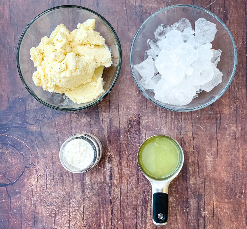 vanilla ice cream, ice cubes, confectioner's sweetener, and fresh lemon juice in a glass bowl