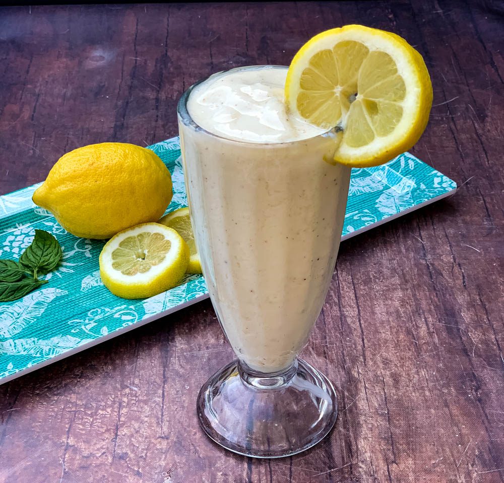chickfila frosted lemonade in a glass cup garnished with a lemon and straw