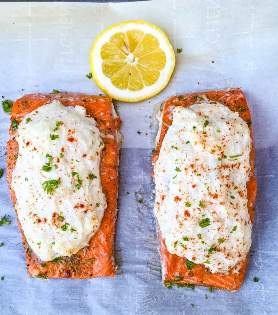 crab stuffed salmon with fresh lemon on parchment paper