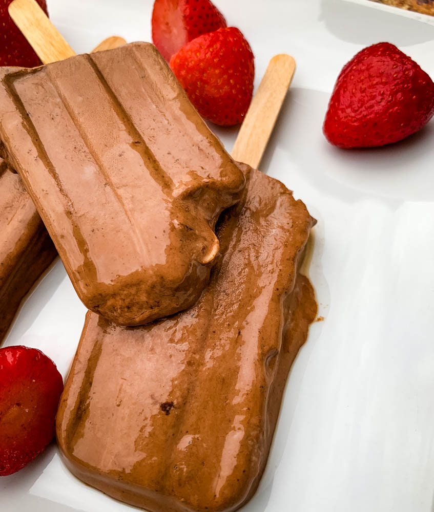 keto low fudge popsicle bars on a white plate with strawberries