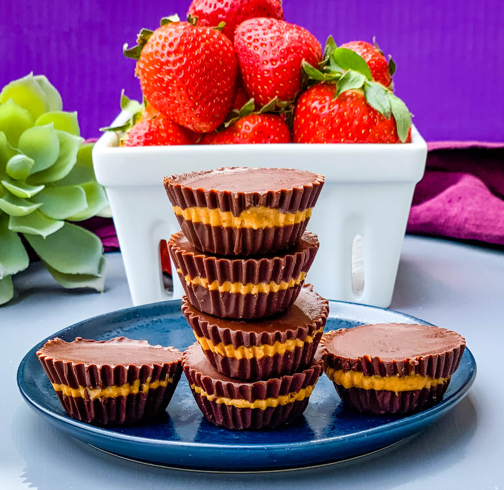 keto peanut butter cups on a blue plate with strawberries