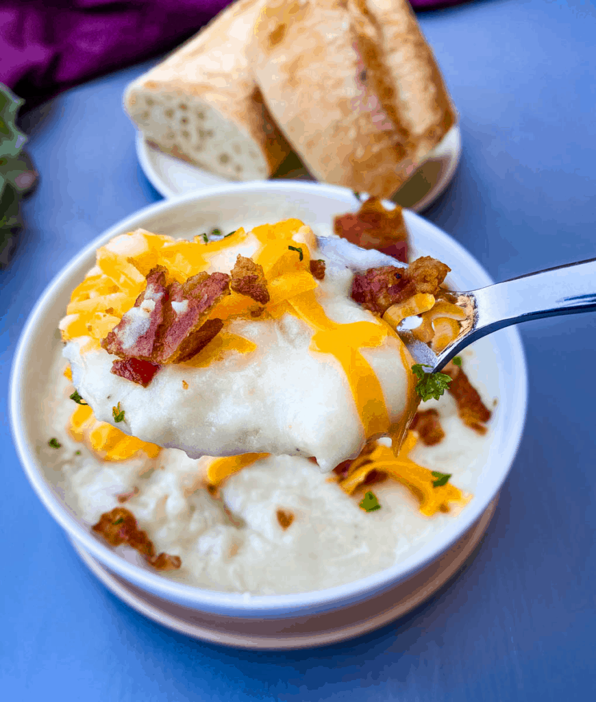 a spoonful of Instant Pot Baked Potato Soup in a white bowl