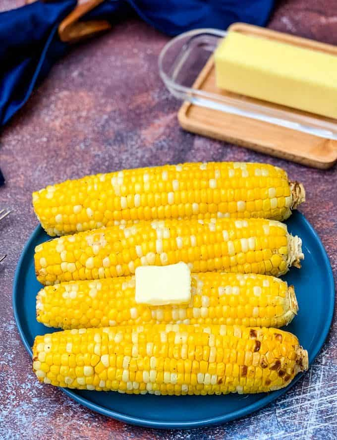 air fryer corn on the cob on a blue plate with butter