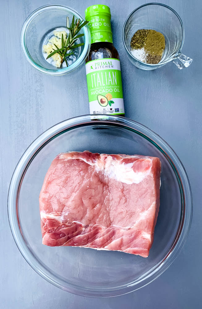 raw pork loin roast, Italian dressing, and seasoning in glass containers