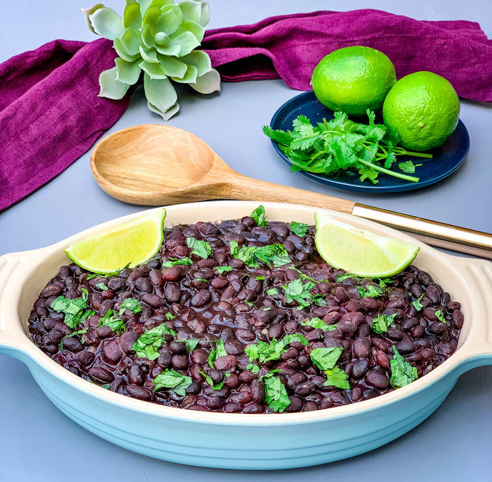 instant pot black beans in a blue bowl with cilantro and lime