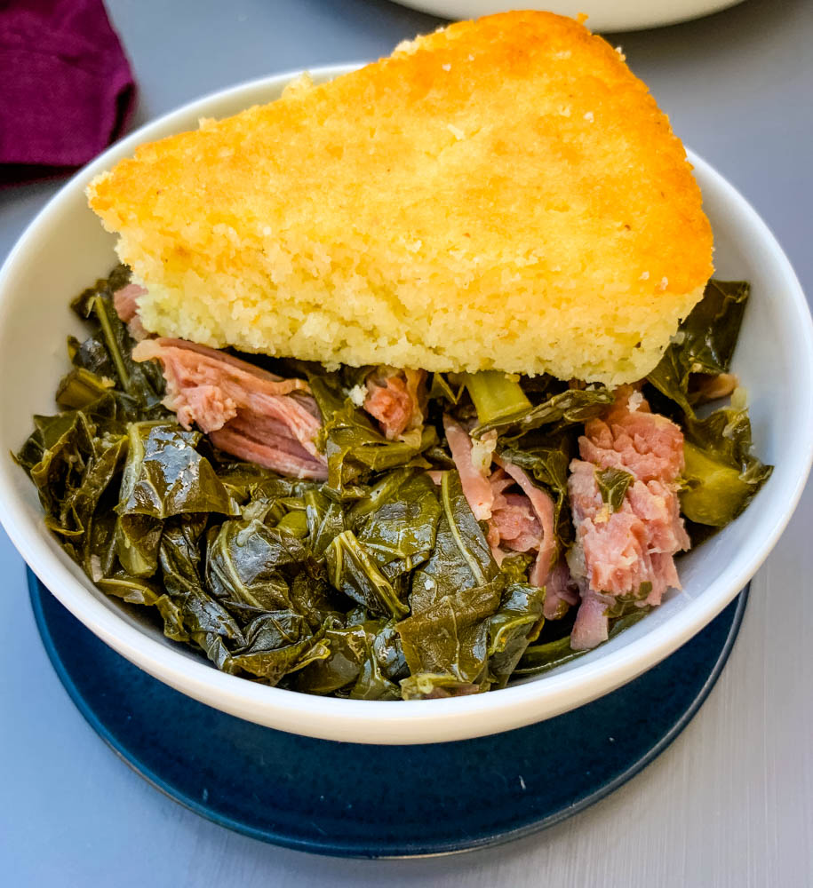 image of collard greens in a white bowl with cornbread