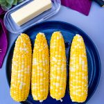 instant pot corn on the cob on a blue plate with a purple napkin