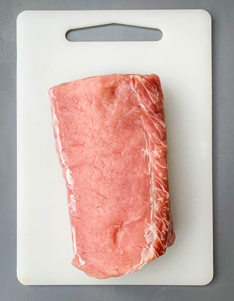 raw pork loin roast on a cutting board