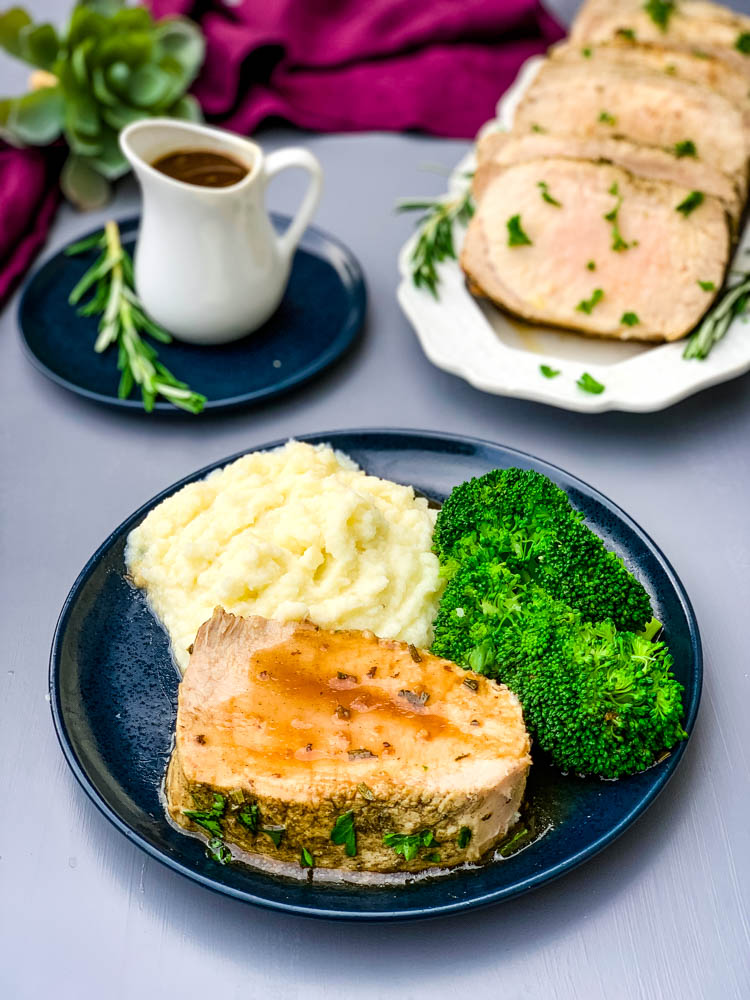 Instant Pot Pork Loin on a blue plate with cauliflower mash and broccoli