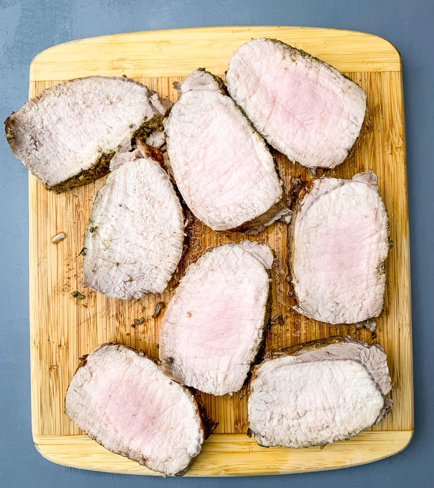 cooked sliced Instant Pot pork loin on a cutting board