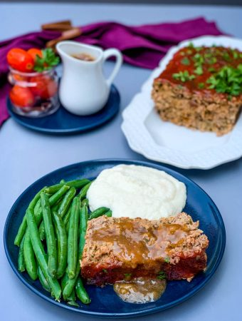 sliced keto low carb meatloaf on a blue plate with mashed cauliflower and blanched green beans