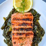pan seared cast iron salmon on a white plate with greens