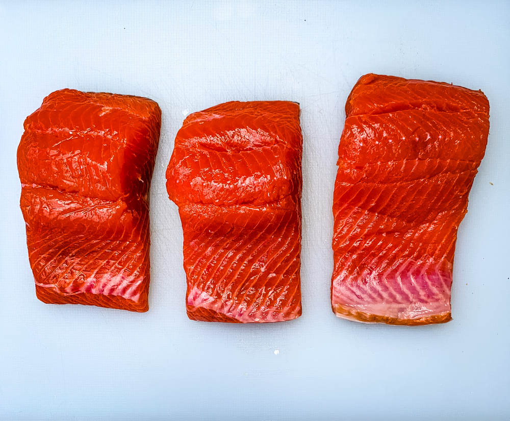 raw salmon fillets on a white cutting board