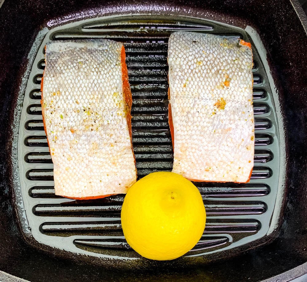 pan seared salmon in a cast iron grill pan skillet with lemon