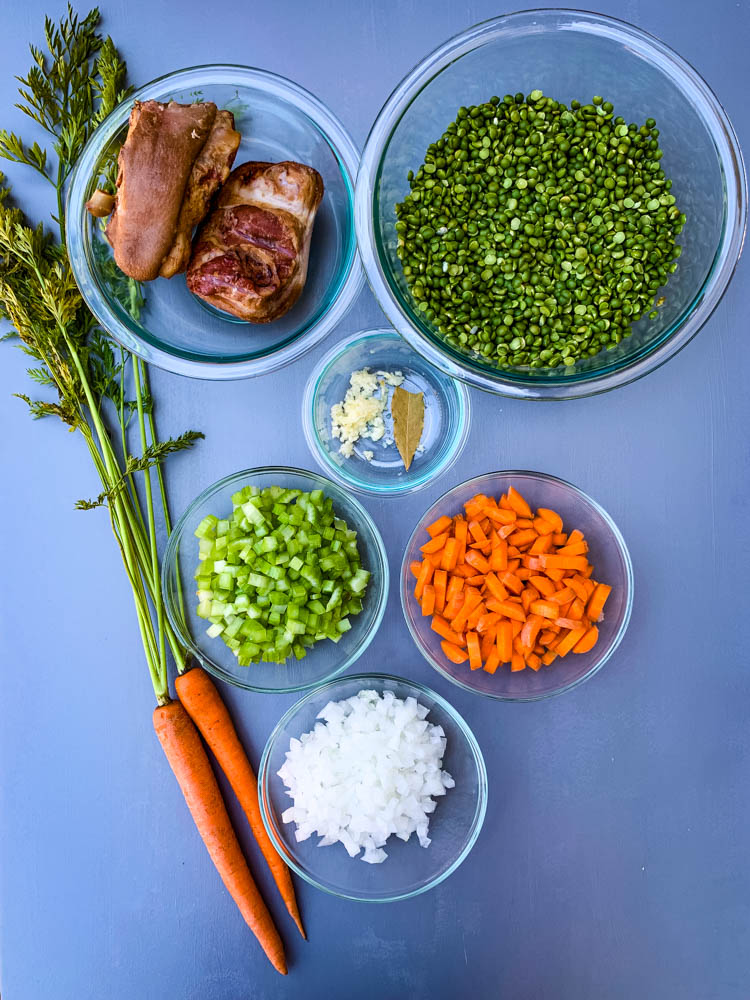 carrots, onions, celery, garlic, split peas, and ham hocks on a flat surface
