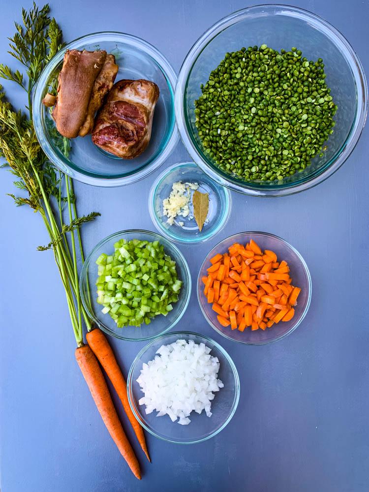 carrots, onions, celery, garlic, split peas, and ham hocks on a flat surface