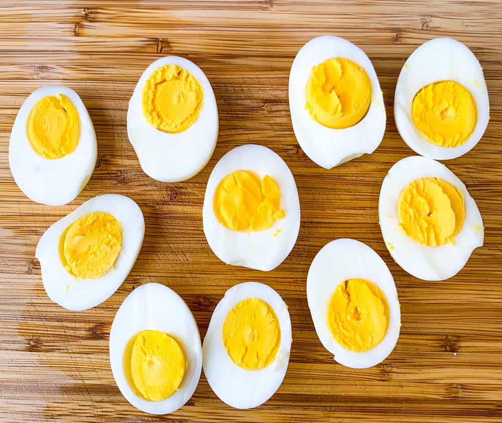air fryer hard boiled eggs sliced on a bamboo cutting board