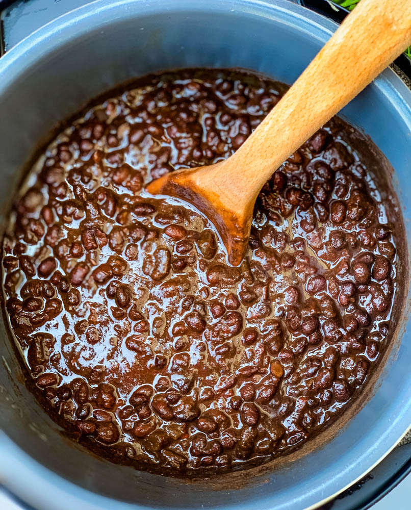 black bean soup in an Instant Pot with a wooden spoon