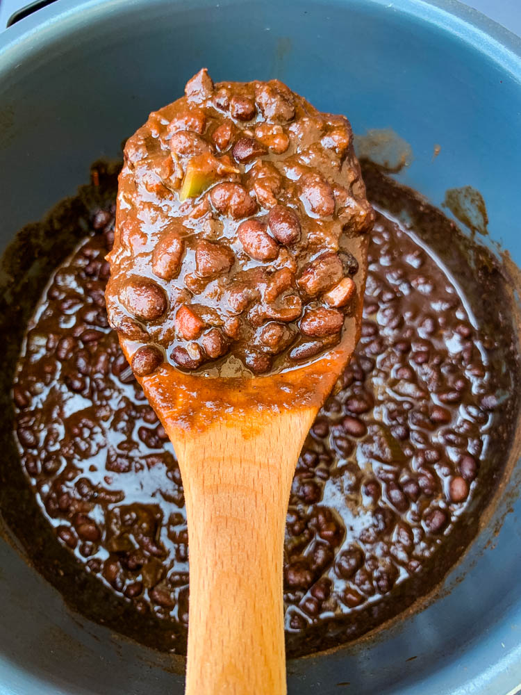 a wooden spoon filled with Instant Pot black bean soup
