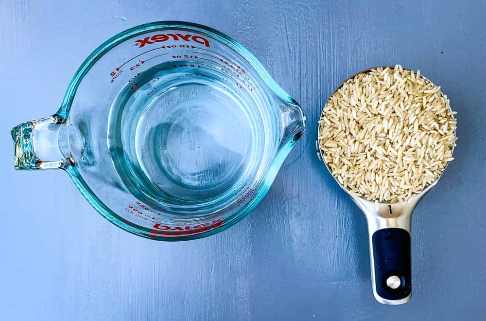 dry brown rice in a measuring cup and a cup of water