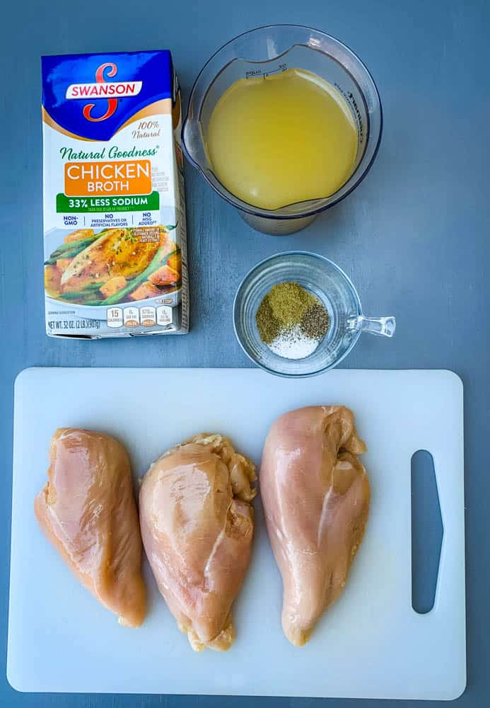 raw chicken breasts on a cutting board with chicken broth and spices and herbs