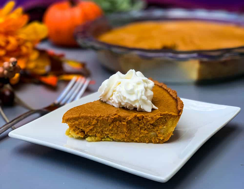 keto low carb pumpkin pie on a white plate with a whole cut pie in the back