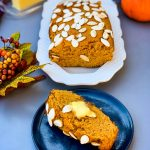 keto low carb pumpkin bread on a white plate with a slice of pumpkin bread on a blue plate