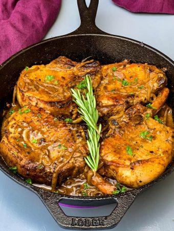 keto low carb smothered pork chops in a cast iron skillet