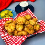 air fryer crunchy fried pickles in a basket with a side of ranch dressing