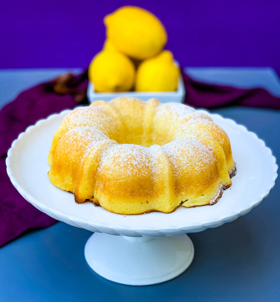 air fryer lemon cake on a white cake stand with fresh lemons