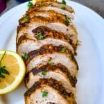air fryer roasted turkey breast on a white plate with sliced lemon