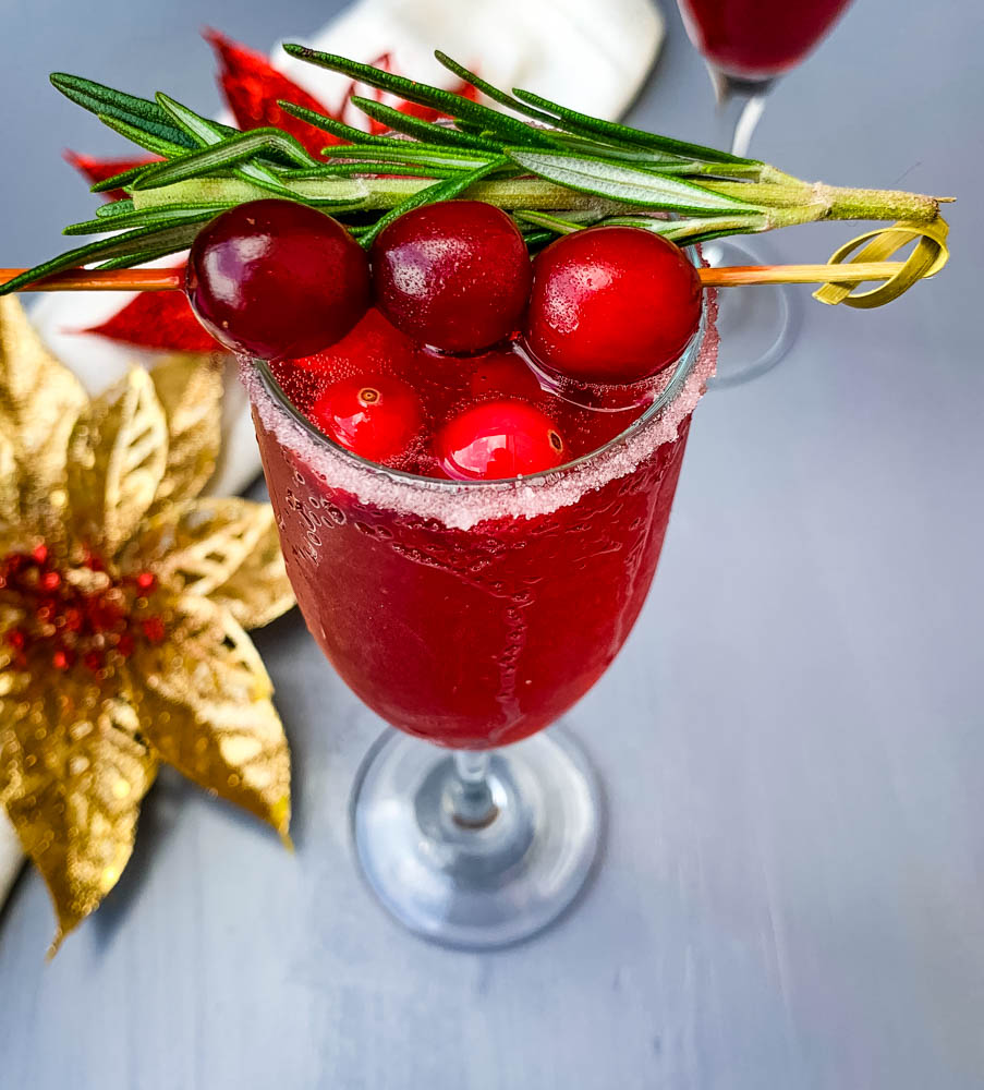 cranberry champagne mimosa in a glass with fresh cranberries