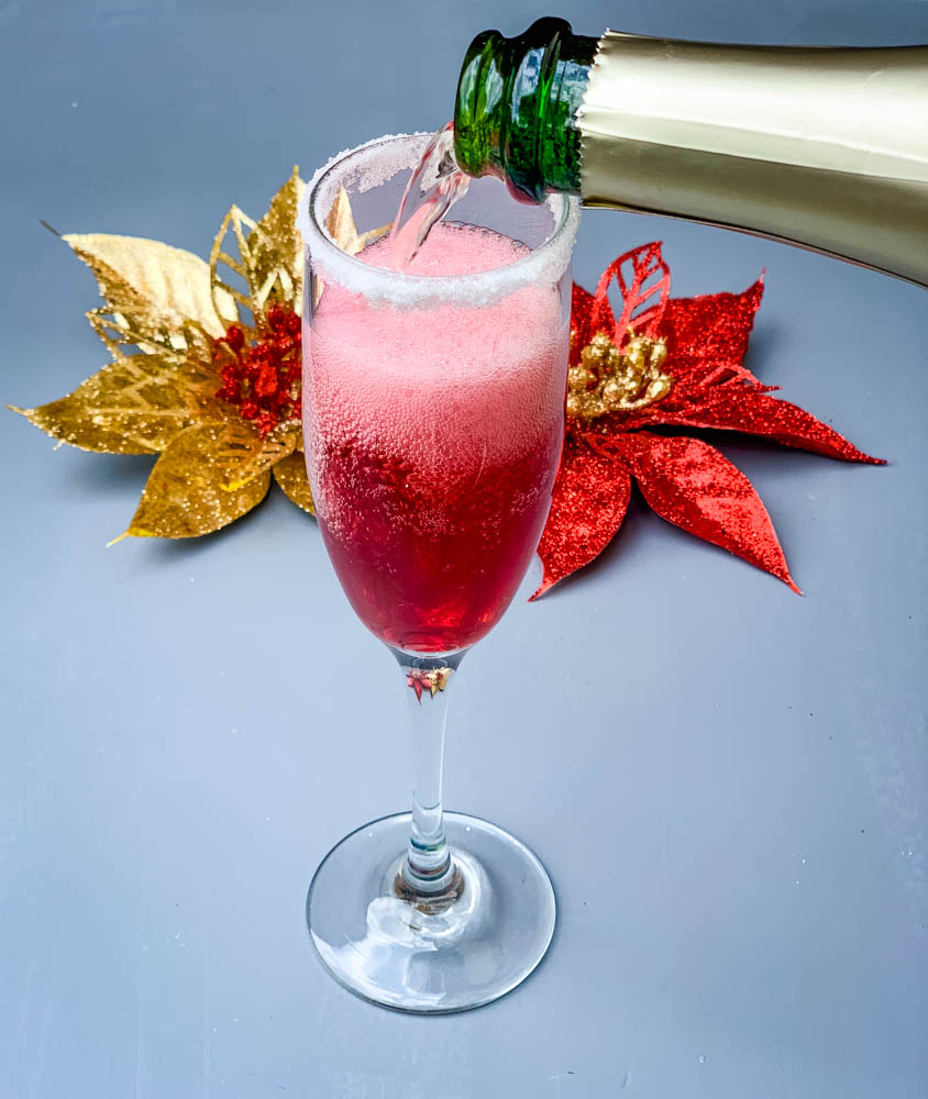 a pour of champagne into a cranberry mimosa